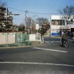 現在の水道端停留所付近:  コンクリ-トの塀と手前のフェンスの間に千川が流れている。青梅街道の向う側の信号の右に暗渠となった千川の遊歩道が続いている。