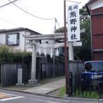 家と家の間に立つ鳥居。その先に参道が続く