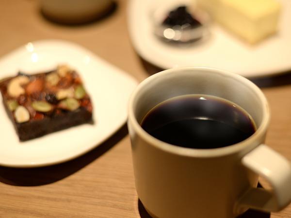 大ぶりのカップたっぷりのコーヒー。チーズケーキやチョコブラウニーを添えて