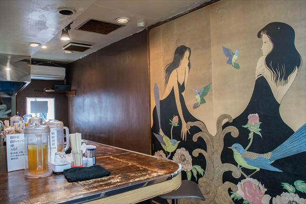 店主の向井さんが前の店舗を自ら改装。広いカウンターと、インパクトある壁画をあえて残している
