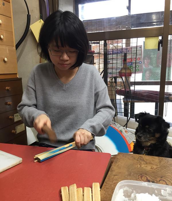 中骨と紙をのりでつける「中付け」をする由香里さん。愛犬「ちーぼぅ」も順扇堂の一員!?職場でいつも一緒だ