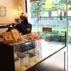神田川遊歩道の木漏れ日が差し込む店内。焙煎機が目をひく。コーヒーのほか、ウサギクッキー(200円)やオリジナル缶バッジ(380円)なども販売