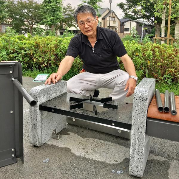 「かまどベンチ」の使い方を説明する公園管理者。近隣住民の避難場所を管理しているという責任感が感じられる